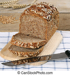 Whole wheat bread on a wooden board and a bread knife