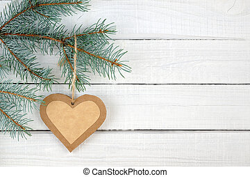 Paper heart and branches of blue spruce on wooden background
