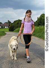 Girl walking her dog - Little girl walking her dog outdoors...