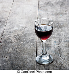 cherry liqueur - glass of cherry liqueur on wooden table