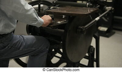 printer using letterpress - man operates a manual...