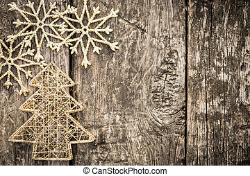 Gold Christmas tree decorations on grunge wood background...