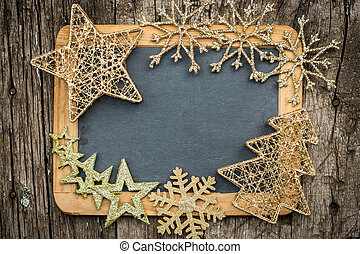 Gold Christmas tree decorations on vintage wooden blackboard...