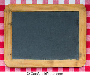 Vintage wooden blackboard on red gingham tablecloth. Copy...