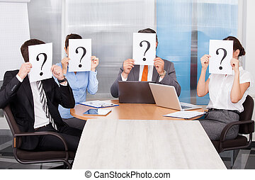 Businesspeople Holding Question Mark Sign - Group Of...