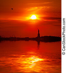 Statue of Liberty and the setting sun - The Statue of...