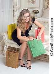 Pretty woman lying on a bed with shopping bags - Pretty...