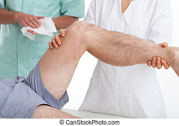 Doctor examining a patient with a painful leg
