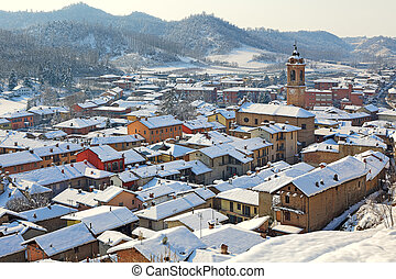 Small town covered with snow in Piedmont, Italy - Roofs of...
