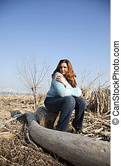 Sitting on a stump - An overweight woman sitting on a stump...