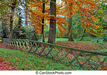 Autumnal park in Italy - Stone fence over small creek and...