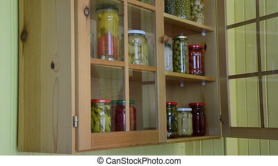 cupboard jar vegetable - hand opens a wooden cupboards door...