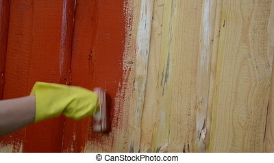 hand brush paint wall - hand in yellow protective glove...