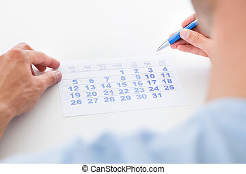 Man With Pen Looking At Calendar - Close-up Of Man Holding...