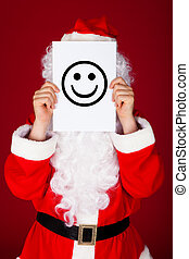 Santa holding smiley in front of his face - Portrait of a...