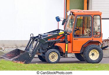 Orange tractor with scoop bucket in the suburbs