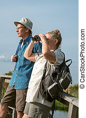Senior Couple Hiking and Birdwatching with Binoculars -...