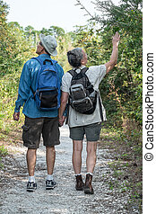 Happy Mature Couple Hiking on Nature Trail Holding Hands -...