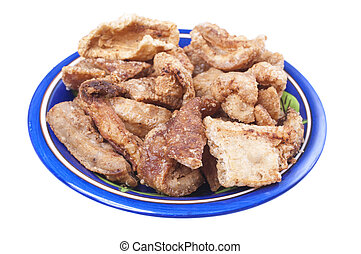 Fried chicharron pork rinds - Closeup of plate of seasoned...