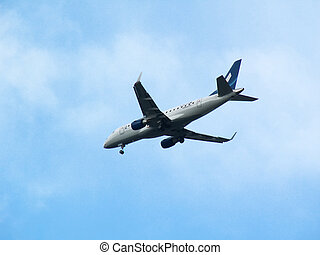 Airplane in the blue sky - White plane descending, on blue...