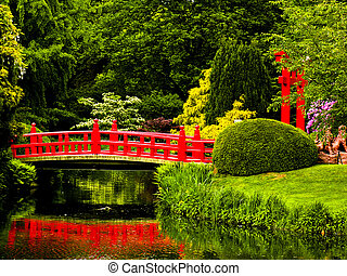 Japanese garden - Red bridge over a lake in green japanese...