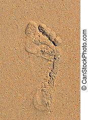 Trace of a bare foot of the person on sand