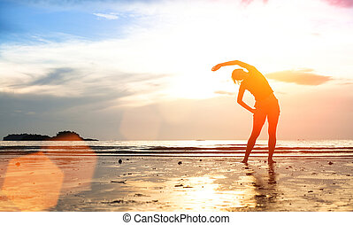 Silhouette young woman, exercise on the beach at sunset (with space for text)