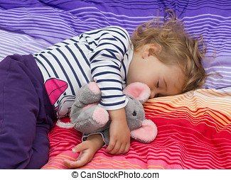 Little girl sleeping with her toy.