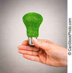 Concept Eco light bulb - Eco light bulb in hand on gray...