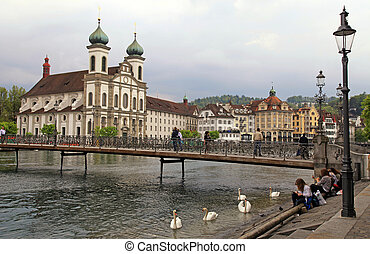 LUCERNE, SWITZERLAND - MAY 06: Cityscape with Jesuit Church and foot bridge on the banks of Reuss River at May 06,2013 in Lucerne, Switzerland.