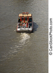 Small boat with a dinghy on the back on a river