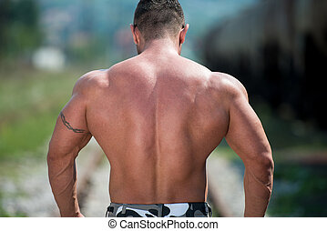 Man Showing Off His Muscle - Bodybuilder Showing His Back...