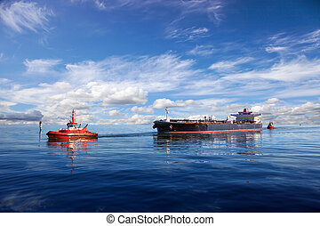 Tanker ship being guided into port by two tugs