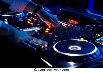 Hands of a DJ mixing music at a disco or concert with one...
