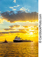 Ship at sunrise - Tug boat pulling the tanker ship at sea.
