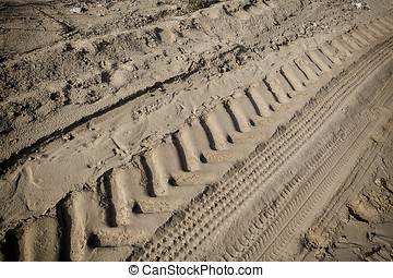 Tractor tire tracks on beach sand. Horizontal shot