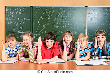 students - Group of happy school children at a classroom...