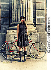 sentiment - Beautiful brunette standing near her old bicycle...