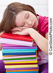 Exhausted young girl asleep on book stack, resting for a...