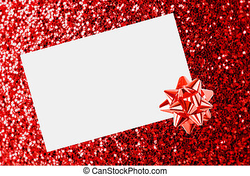 Christmas sheet of paper with bow on red defocused...