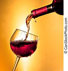 pouring red wine in the glass tilted on golden background