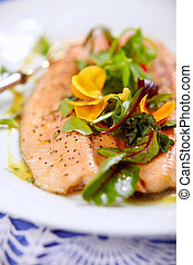 steamed trout and beet leaves on white plate