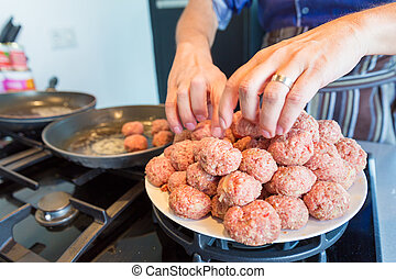 Chef putting meatballs in a frying pan