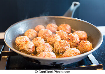 Meatballs in the frying pan on the gas stove