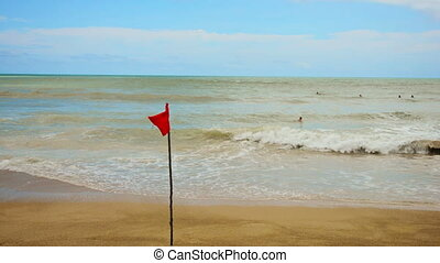 Red flag on the beach during a storm - swimming is prohibited