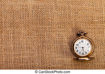 Classic pocket watch on burlap - Antique pocket watch on...
