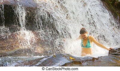 Funny woman swims in the forest waterfall. Thailand. Phuket