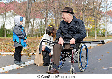 Woman and her son helping a disabled old man - Woman and her...