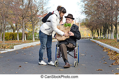 Man in a wheelchair being helped with groceries - Senior man...