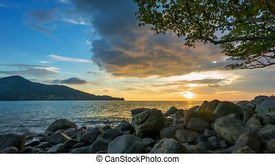 Tropical sea coast with stones and tree at sunset. Thailand. Kamala Beach